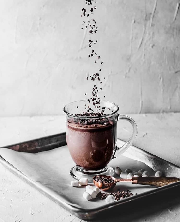 clear mug with hot chocolate on top of a black baking tray with a layer of parchment. chocolate sprinkles are suspended in midair